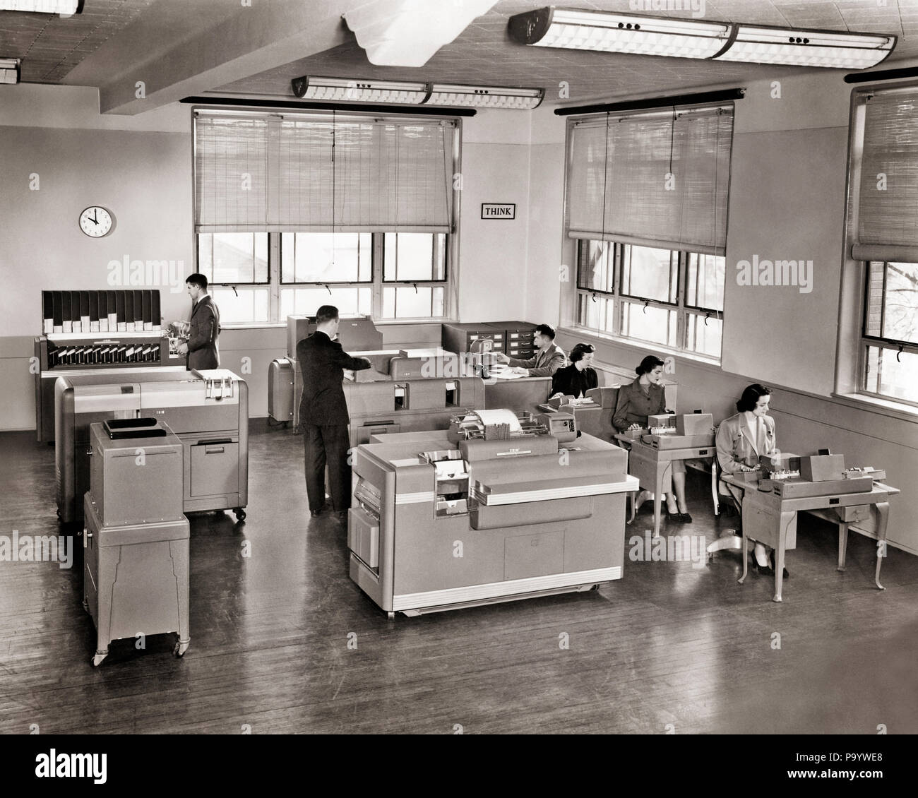 1950s THINK SIGN ON WALL IBM OFFICE INTERIOR MEN WOMEN WORKING EARLY DATA PROCESSING INSTALLATION INFORMATION SYSTEM TECHNOLOGY - q74730 CPC001 HARS SPEED FIVE HISTORY FEMALES 5 IBM GROWNUP COMMUNICATING COPY SPACE FULL-LENGTH LADIES COMPUTERS PERSONS INSPIRATION GROWN-UP MALES PROFESSION CONTEMPLATING B&W WORK PLACE DATA DECORATION PROCESSING DECOR OCCUPATION EARLY STRENGTH CUSTOMER SERVICE NETWORKING KNOWLEDGE POWERFUL PROGRESS THINK INNOVATION PRIDE OCCUPATIONS HIGH TECH PONDER PONDERING STYLISH TRADEMARK CONTEMPLATIVE COMMUNICATE CONTEMPLATE COOPERATION CREATIVITY HIGH-TECH IDEAS MID-ADULT - Stock Image