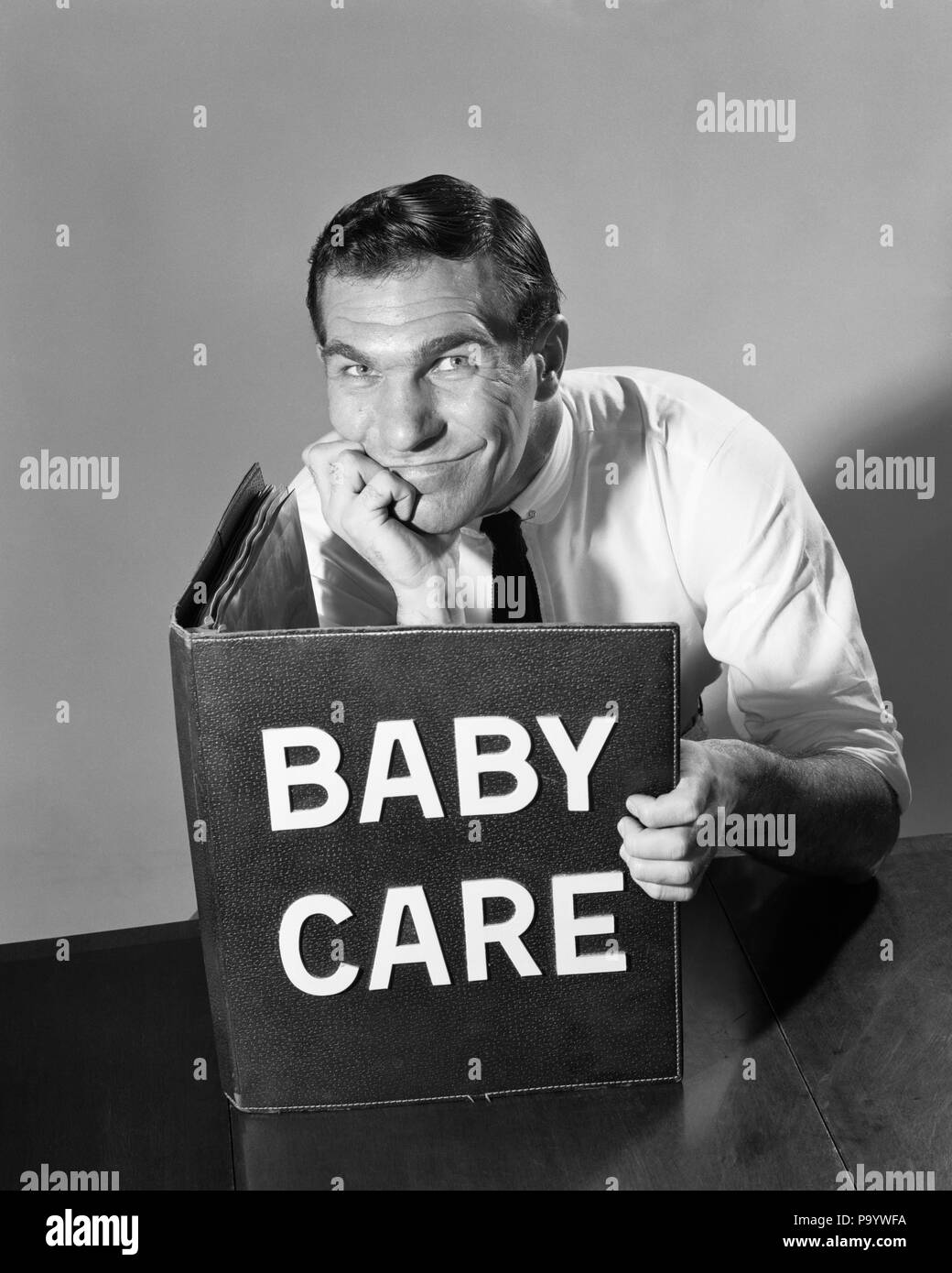 1950s 1960s MAN FATHER HAND ON CHIN READING LARGE BOOK TITLED BABY CARE SMILING LOOKING AT CAMERA - s10171 DEB001 HARS OLD FASHION 1 JUVENILE FACIAL FEAR COMMUNICATION INFORMATION MYSTERY GROWNUP COMMUNICATING PERSONS INSPIRATION GROWN-UP CHIN CONFIDENCE EXPRESSIONS FATHERS B&W SINGLE PARENT SINGLE PARENTS ADVENTURE MANUAL EXCITEMENT KNOWLEDGE DIRECTION TITLED DEB001 BEFUDDLED COMMUNICATE MID-ADULT MID-ADULT MAN SOLUTIONS YOUNGSTER BLACK AND WHITE CAUCASIAN ETHNICITY OLD FASHIONED - Stock Image