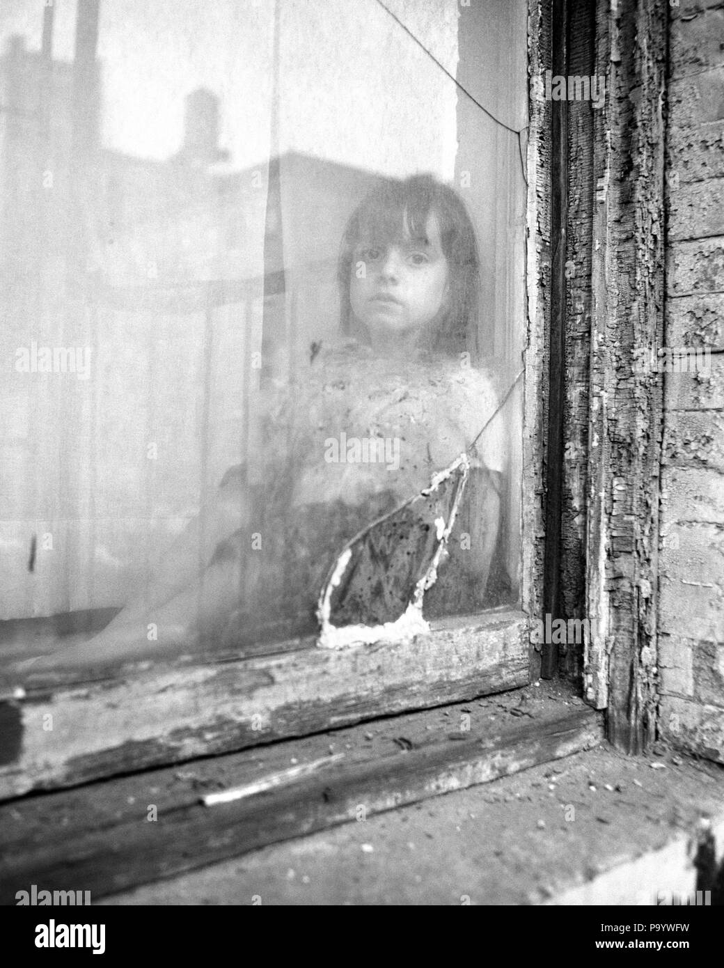 1970s poor little girl looking at camera out of broken window of slum apartment w5864
