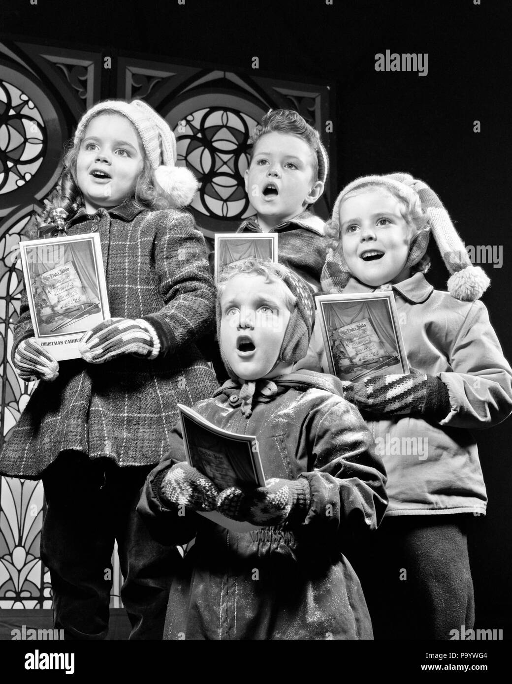 1950s TWO GIRLS TWO BOYS SINGING CHRISTMAS CAROLS - x191 HAR001 HARS HOME LIFE FRIENDSHIP HALF-LENGTH INSPIRATION CARING MALES ENTERTAINMENT SIBLINGS SPIRITUALITY CONFIDENCE SISTERS B&W CAROLS HAPPINESS EXCITEMENT RECREATION PRIDE SIBLING CAROLING STYLISH CREATIVITY GROWTH JUVENILES TOGETHERNESS BLACK AND WHITE CAUCASIAN ETHNICITY HAR001 OLD FASHIONED - Stock Image