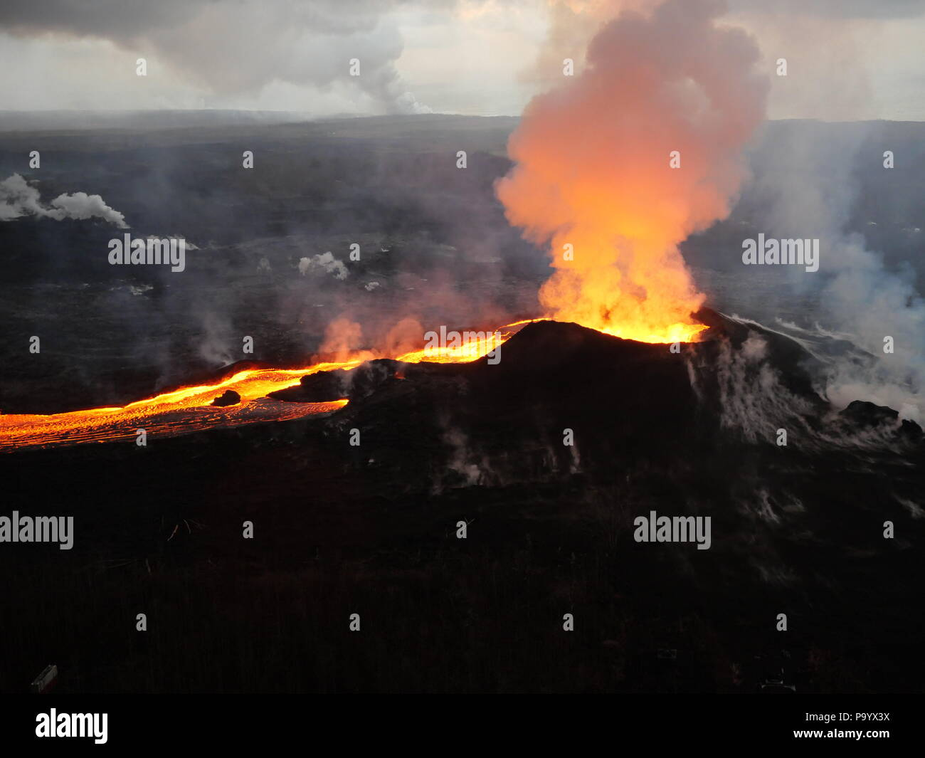 Lava and ash pour out from fissure 8 as a lava channel flows toward the ocean caused by the Kilauea volcano eruption July 14, 2018 in Hawaii. Stock Photo