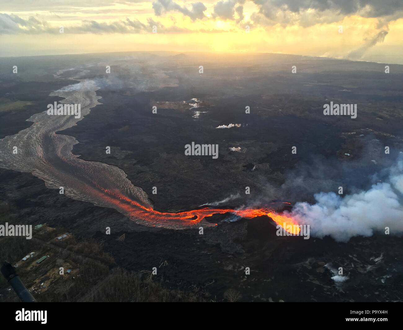 Lava and ash pour out from fissure 8 as a lava channel flows toward the ocean caused by the Kilauea volcano eruption July 17, 2018 in Hawaii. - Stock Image