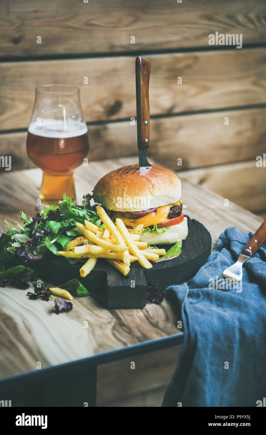 Classic burger dinner with glass of beer and french fries - Stock Image
