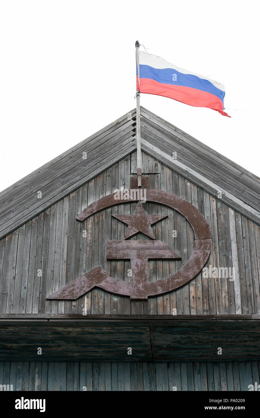 Russian Flag above old Soviet Hammer and Sickle in small Russian Village in Kamchatka - Stock Image
