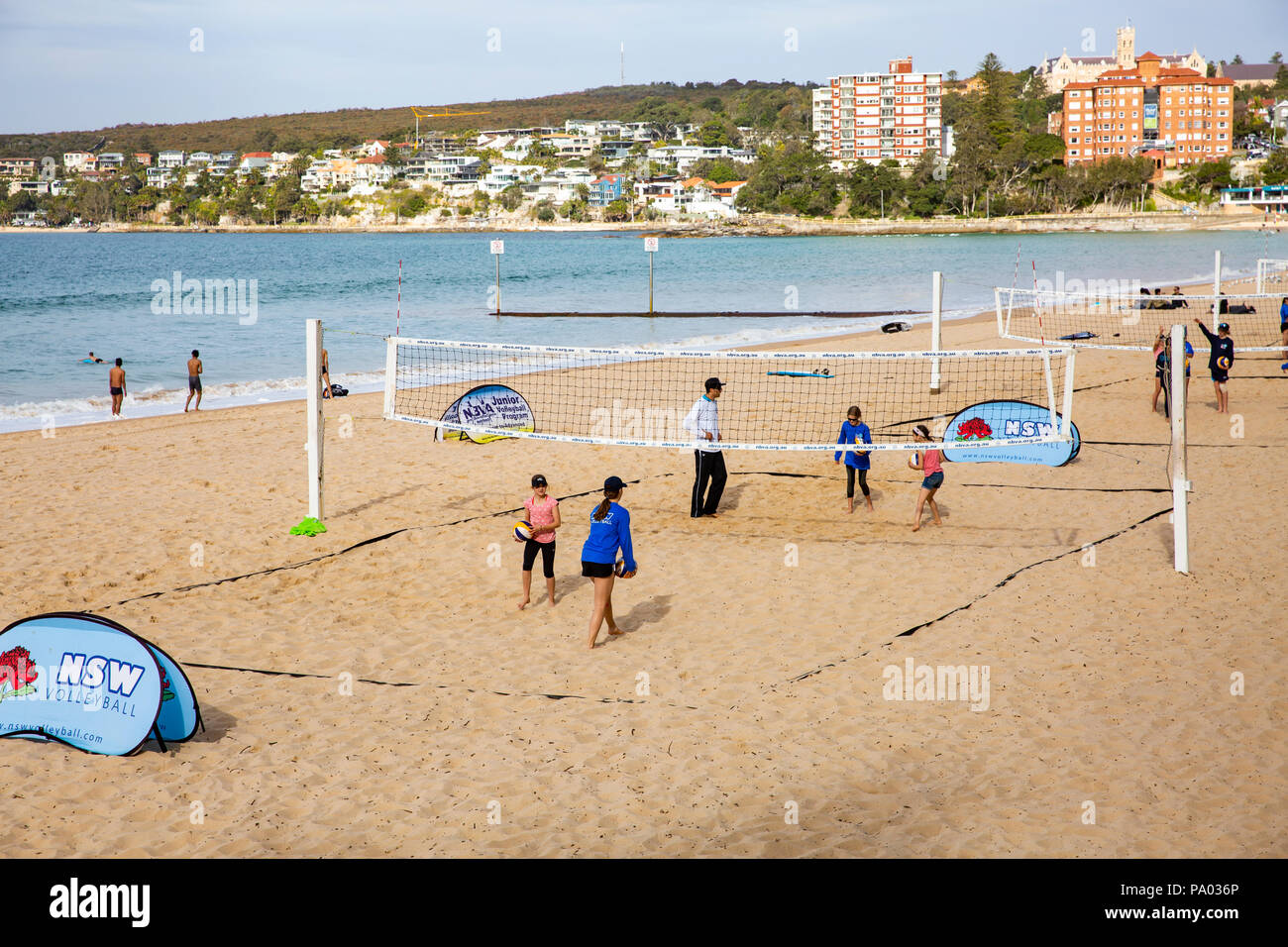 Children learning beach volleyball during school holidays on Manly beach in Sydney,Australia - Stock Image