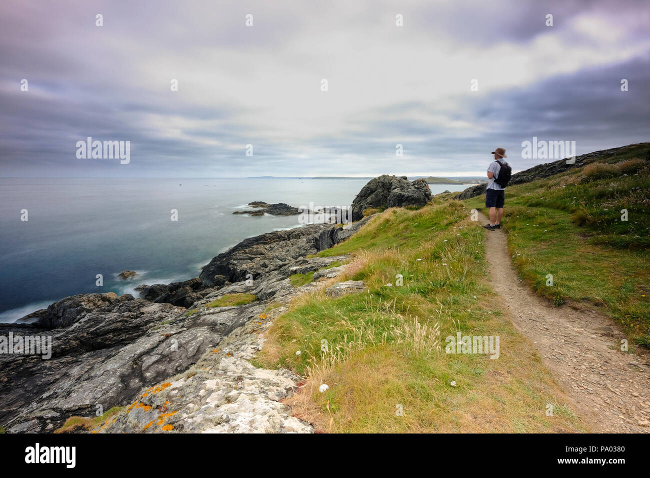 Man walking alonfg the south west coast path close to St Ives taking in the view - Stock Image