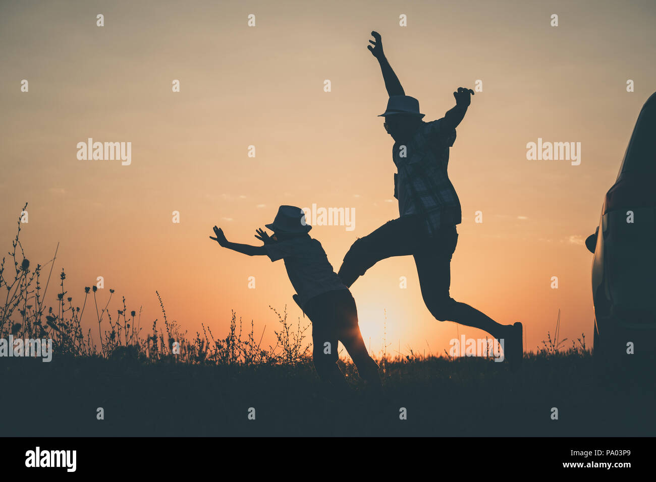 Father and son playing in the park at the sunset time. People having fun outdoors. Concept of summer vacation and friendly family. - Stock Image
