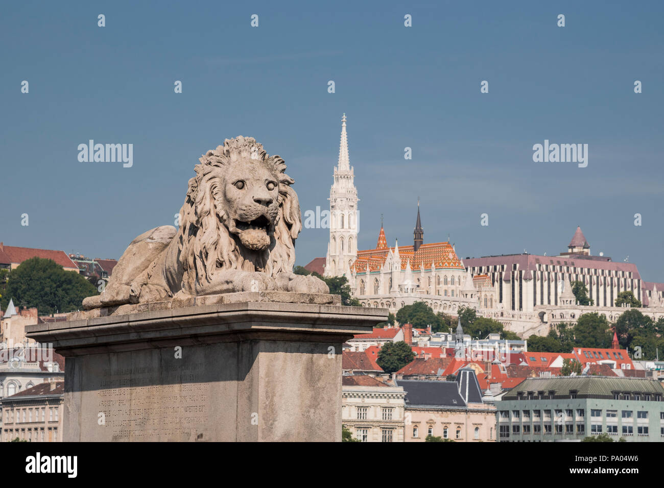 Lion sculpture on Chain Bridge with St Matthias Church and Fisherman's Bastion in background, Budapest, Hungary Stock Photo