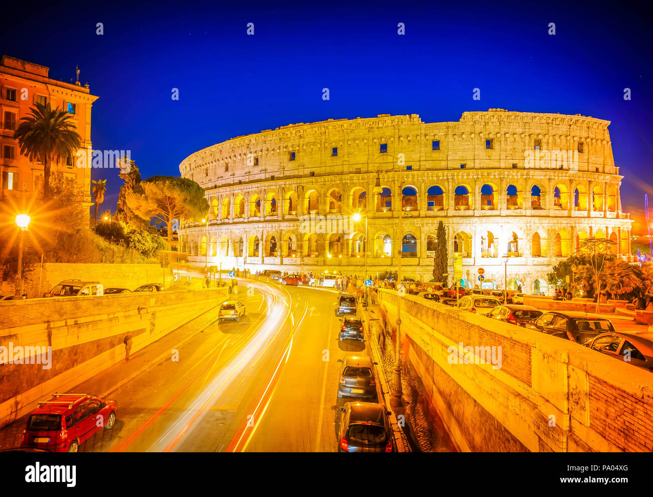 view of Colosseum illuminated at nighwith traffic lightst in Rome, Italy, retro toned - Stock Image
