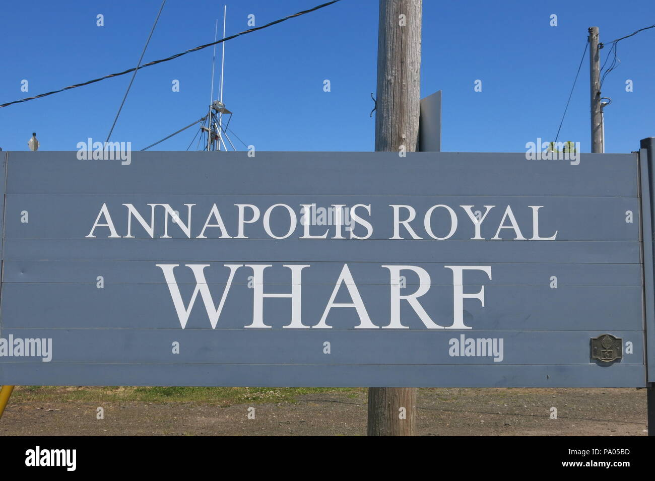 White capital letters on a smart grey wooden board signpost that you're at Annapolis Royal Wharf, Nova Scotia, Canada - Stock Image