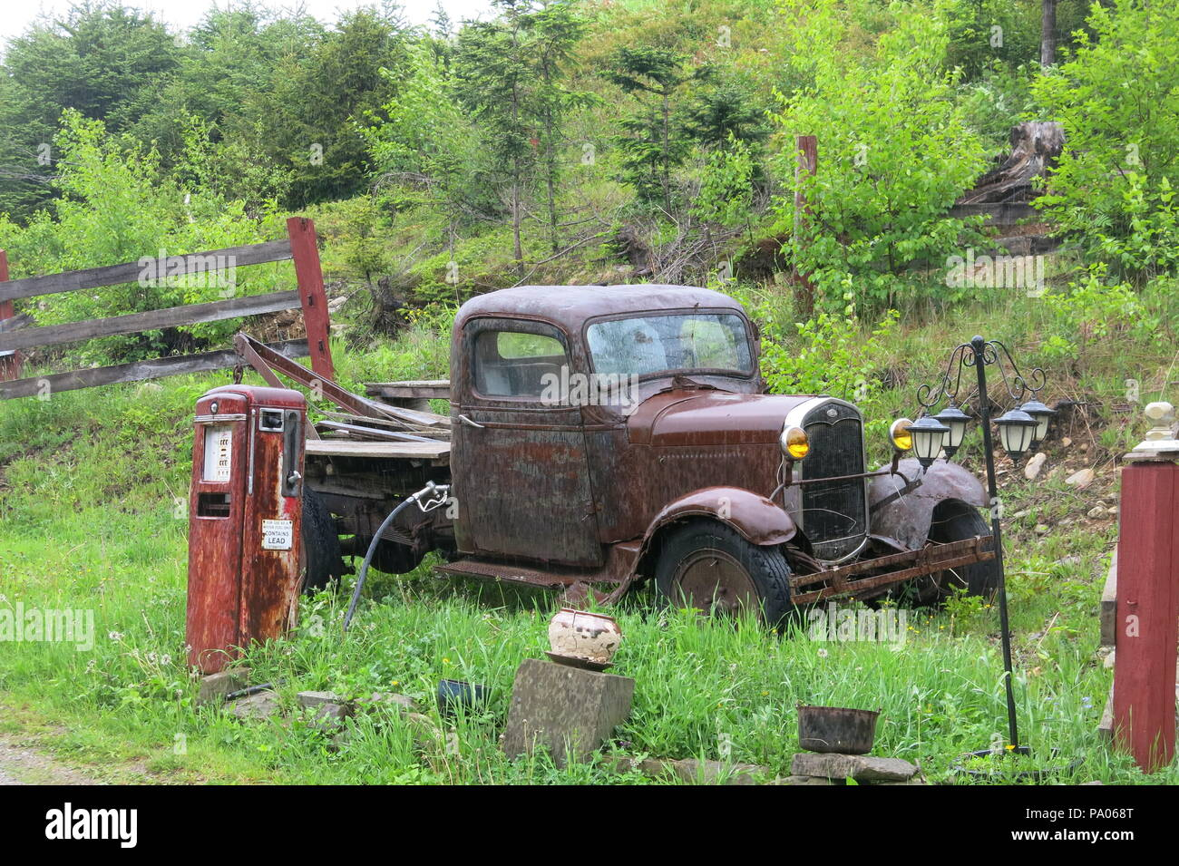 This ancient Ford tow-truck and old-fashioned petrol pump, abandoned in the countryside, make a vintage scene and memories of a bygone era. - Stock Image