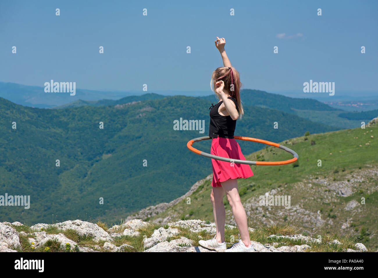 Young woman in pink skirts rotates hula hoop at the mountain top on beautiful nature background. Healthy lifestyle and love for fitness and sport. Fre - Stock Image