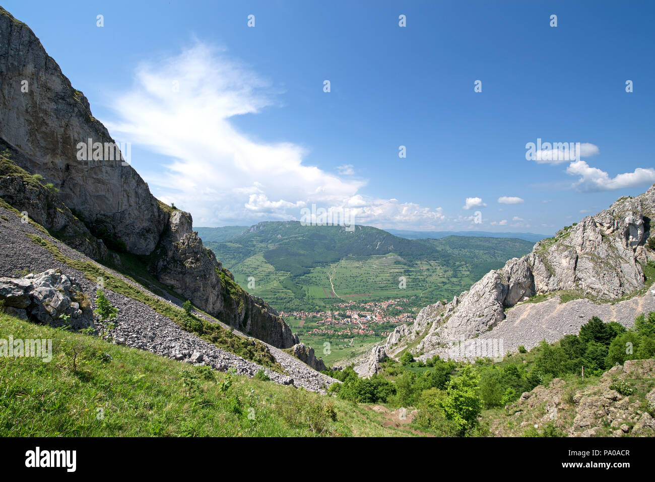 Sunny summer day at mountain peak, where tourists climb to conquer fear, find courage and develop lateral thinking skills to overcome difficulty of cl - Stock Image