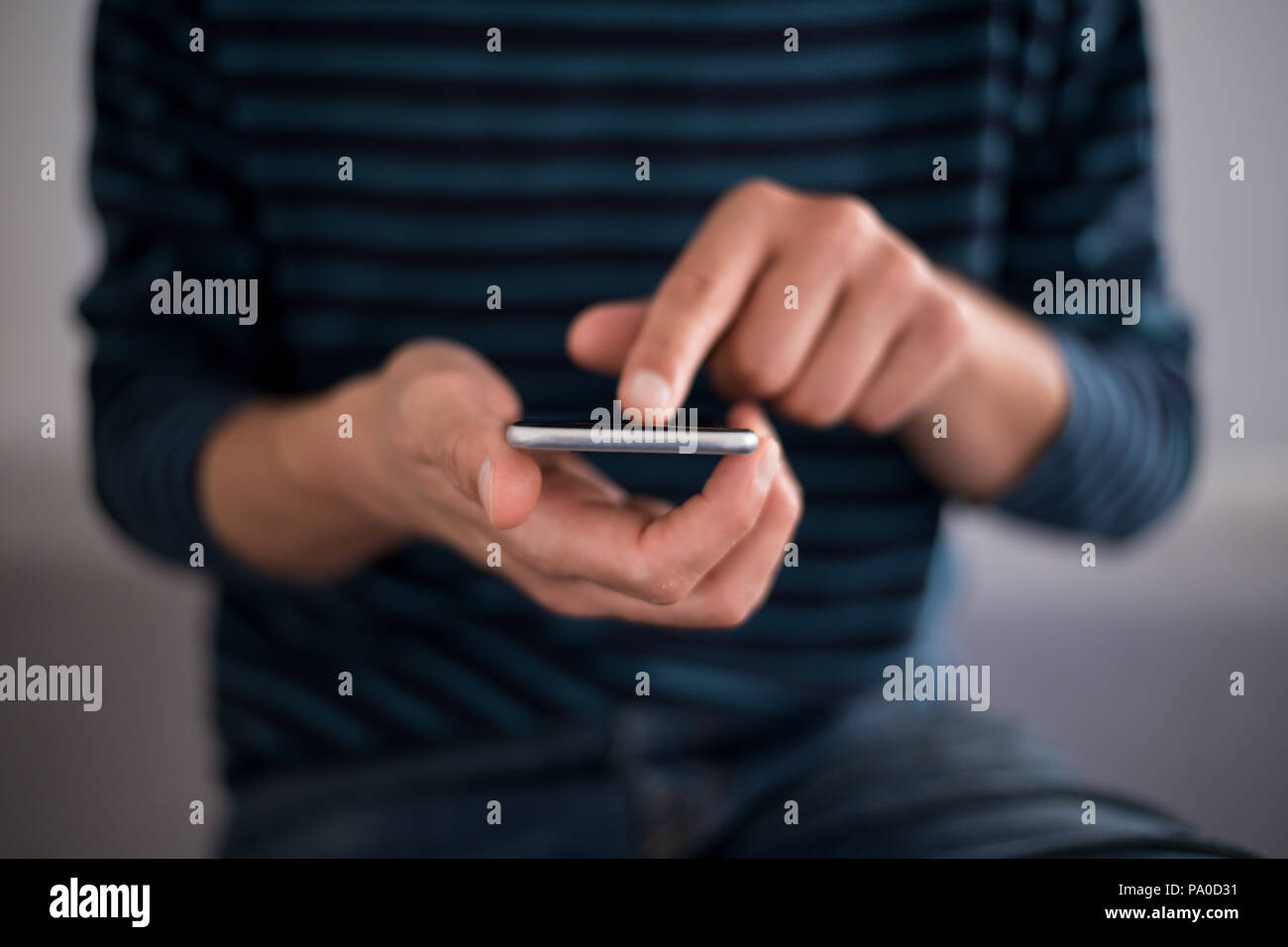 Young man using a touchscreen smartphone - Hands close-up - Using technology - Stock Image
