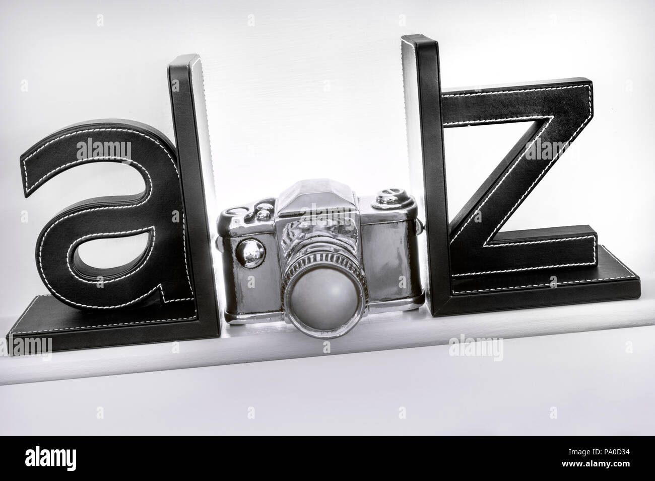A-Z stylised generic silver camera on bookshelf as Guide to Cameras Photography Photographic Techniques Film Cherished Classics Stock Photo