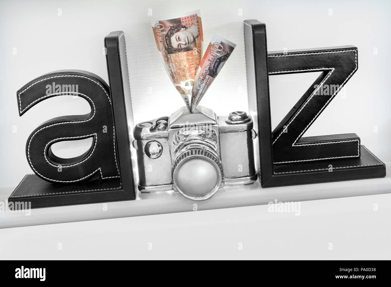 Concept A-Z  'make money from your camera'  Photography images that sell. £10 notes going into savings slot in top of concept style silver  camera - Stock Image