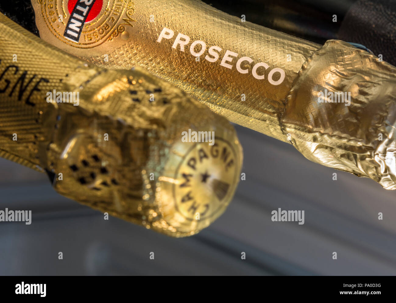 Close up on featured Prosecco name on foil neck sparkling wine bottle with Champagne bottle neck de-focused in foreground in chilled wine cabinet Stock Photo