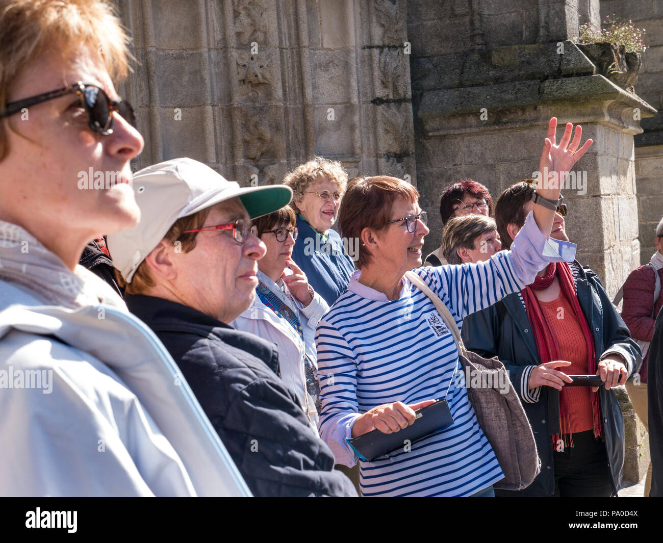 Tour Guide with her all-female tour group in full flow outside Quimper Cathedral, properly the Cathedral of Saint Corentin of Quimper Brittany France - Stock Image