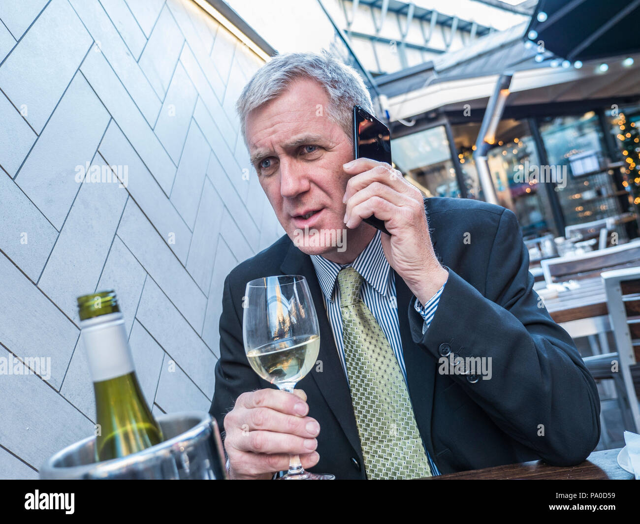 Mature city executive businessman, looking worried listening on his iPhone 7 plus mobile telephone at alfresco restaurant holding glass of white wine - Stock Image