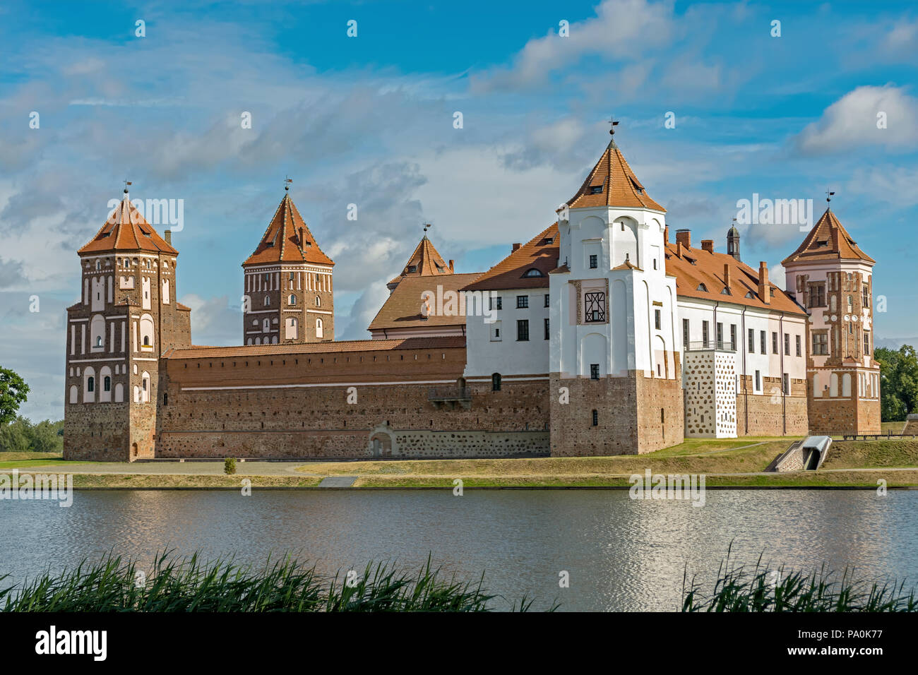 Mir castle complex in the city of Mir in Belarus against a blue sky and a pond in the foreground. - Stock Image