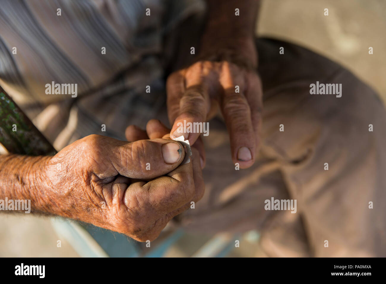 Close up shot of man cleaning fingernails with razor blade, Vinales, Pinar del Rio Province, Cuba - Stock Image