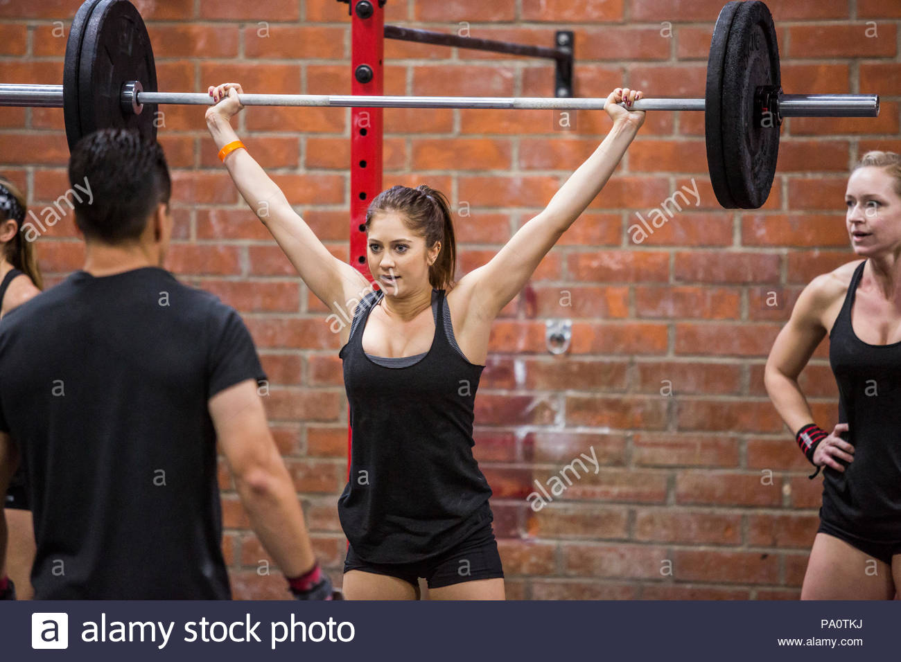 Female CrossFit athlete with barbell overhead - Stock Image