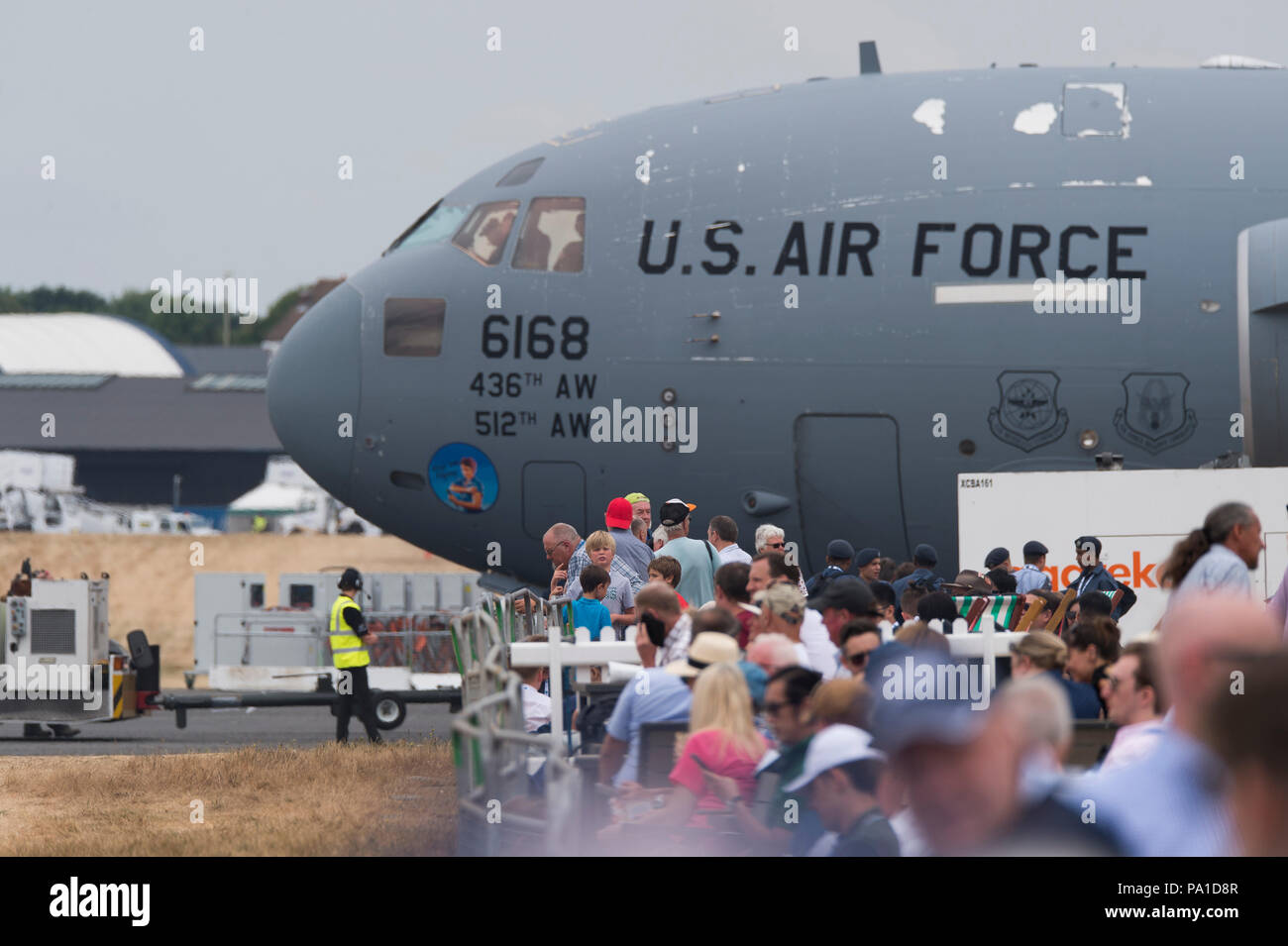 Farnborough, Hampshire, UK. 20 July, 2018. Final day of the biennial Farnborough International Trade Airshow FIA2018, typically a transition day as business customers leave in VIP jets and members of the public arrive to watch the build-up for the weekend public airshow. A large Boeing C-17 Globemaster III military transport aircraft of the US Air Force parks up, towering over spectators Credit: Malcolm Park/Alamy Live News. - Stock Image