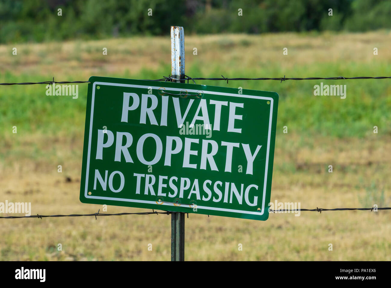 Private property warning sign hanging on barb wire fence, Castle Rock Colorado US. - Stock Image