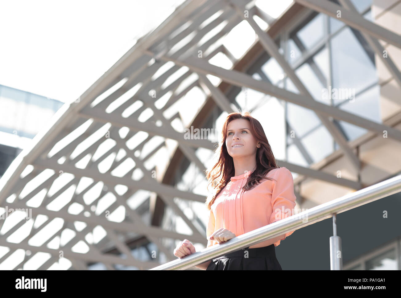 modern business woman standing on the balcony of a modern office building - Stock Image
