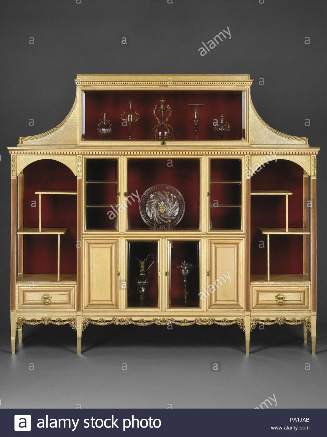 Cabinet, ca. 1883, Made in New York, New York, United States, American, Maple, with painted and gilded surface, bevelled glass, silk velvet, brass, 64 1/2 x 71 x 14 1/2 in. (163.8 x 180.3 x 36.8 cm), Furniture, Attributed to Herter Brothers (German, active New York, 1864–1906), This drawing-room cabinet exemplifies the ivory and gold palette Herter Brothers favored in drawing rooms designed for their wealthy clients, such as Oliver Ames, industrialist and governor of Massachusetts, for whom this piece was made. - Stock Image