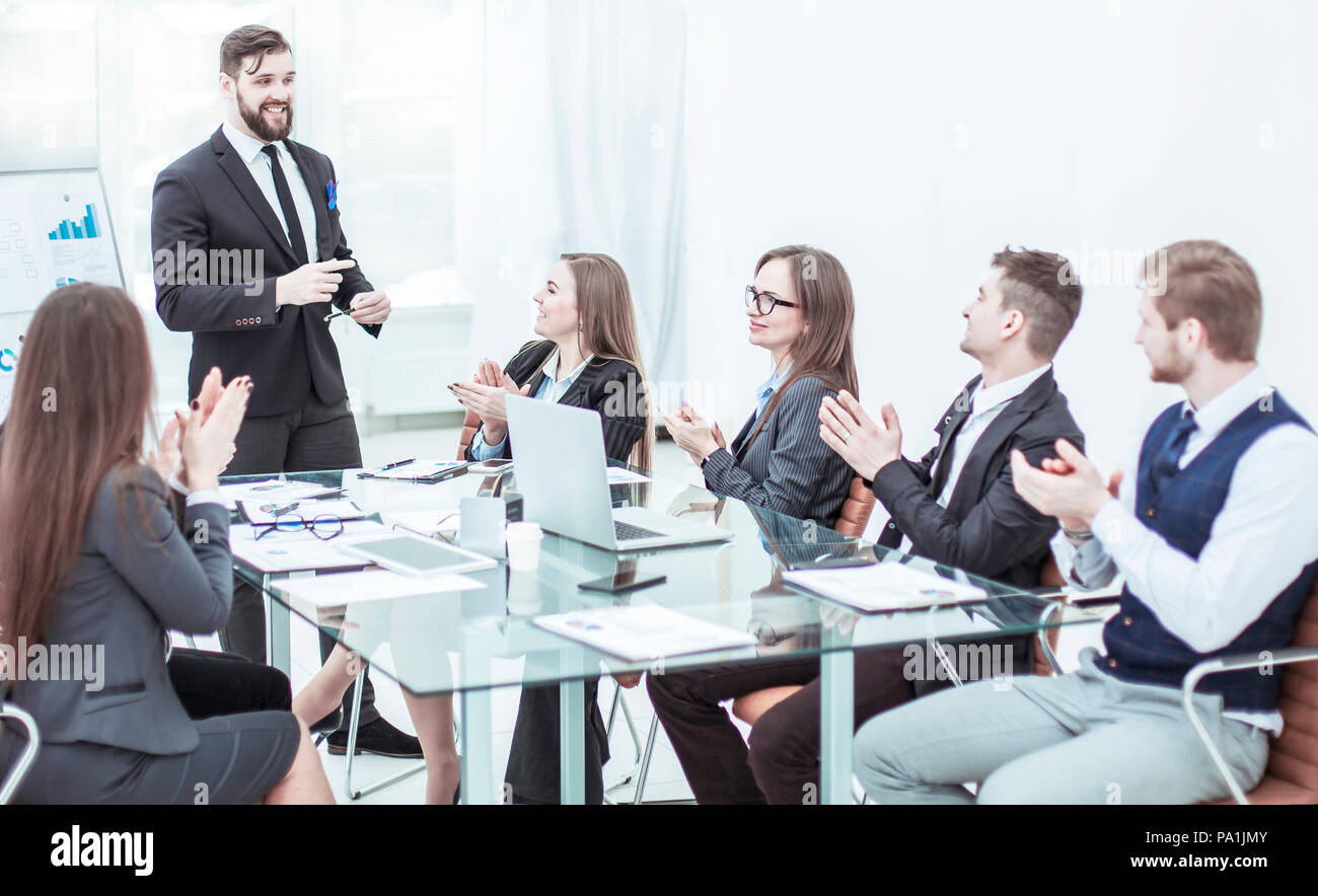 business team applauding to the Manager Finance on the presentation of the new project in the workplace - Stock Image