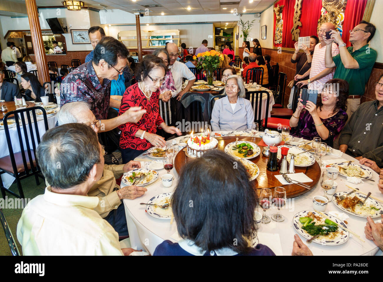 Orlando Florida Chinatown Lam's Garden Chinese restaurant dim sum ethnic dining large family lazy Susan table Asian man woman special event celebratio - Stock Image