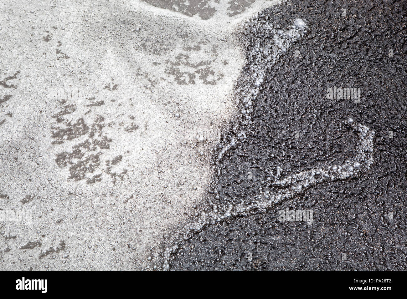 Aeration of wasterwater producing a cover of bubbles and foam coated in brown-black sludge - Stock Image