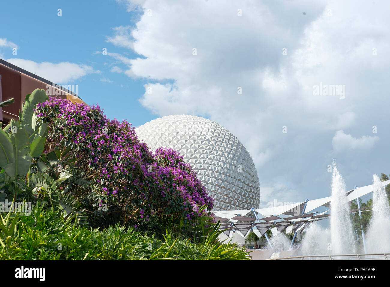 Epcot Center Spaceship Earth, sometimes called The Giant Golf Ball, is seen from an unusual angle, with room for text in the blue sky. Water fountains - Stock Image