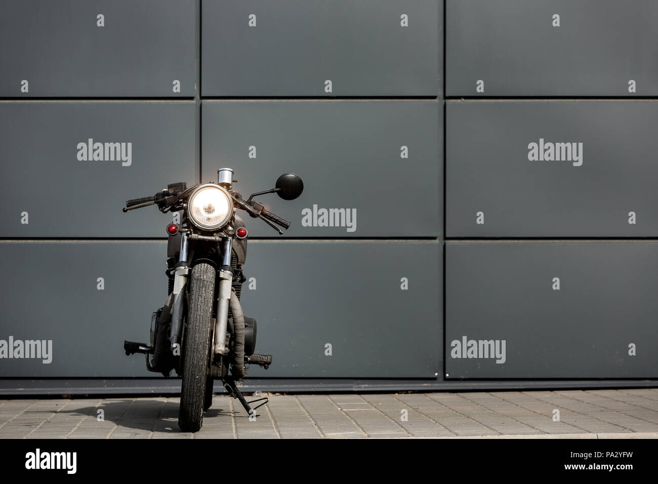 Custom motorcycle parking near gray wall of industrial building. Everything is ready for having fun driving the empty road on a motorcycle tour journe - Stock Image