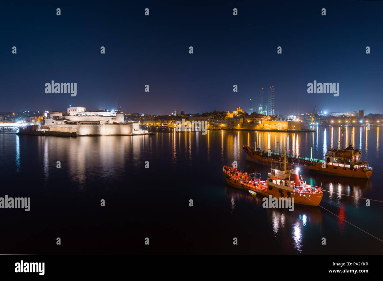 Valletta port at night with anchored ships and Vauban fort, in Malta. - Stock Image