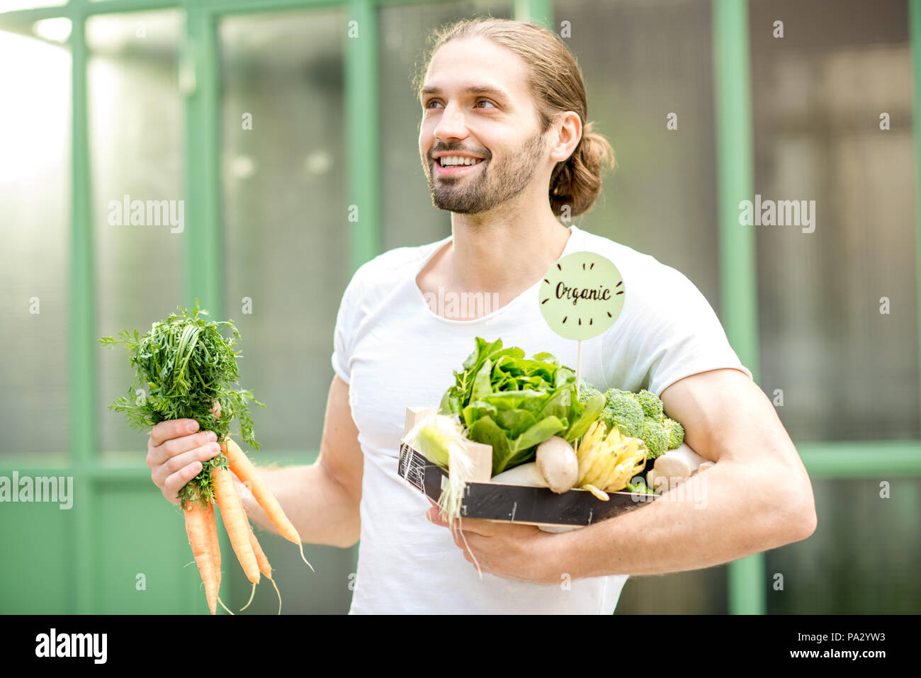 Portrait of a happy vegetarian man holding box full of fresh raw vegetables outdoors on the green background - Stock Image