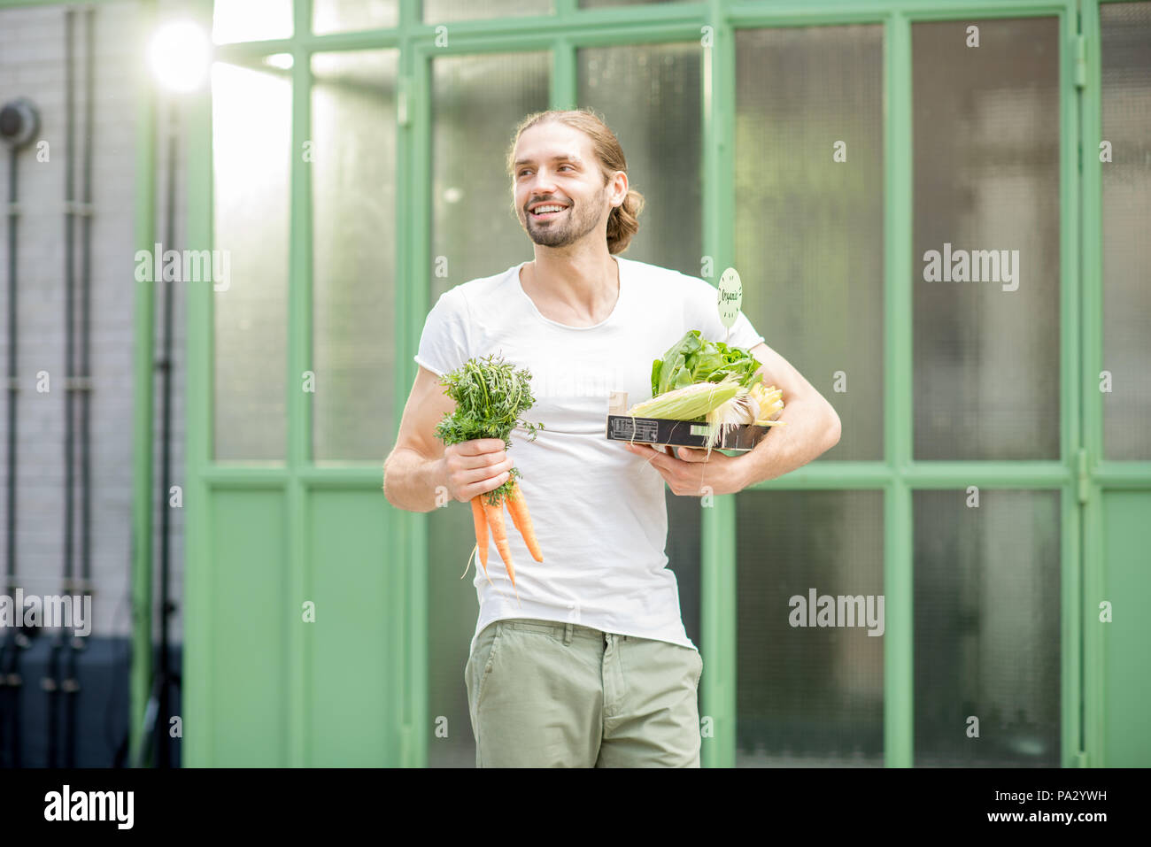 Man carrying box full of fresh raw vegetables just bought at the local market outdoors on the green background Stock Photo