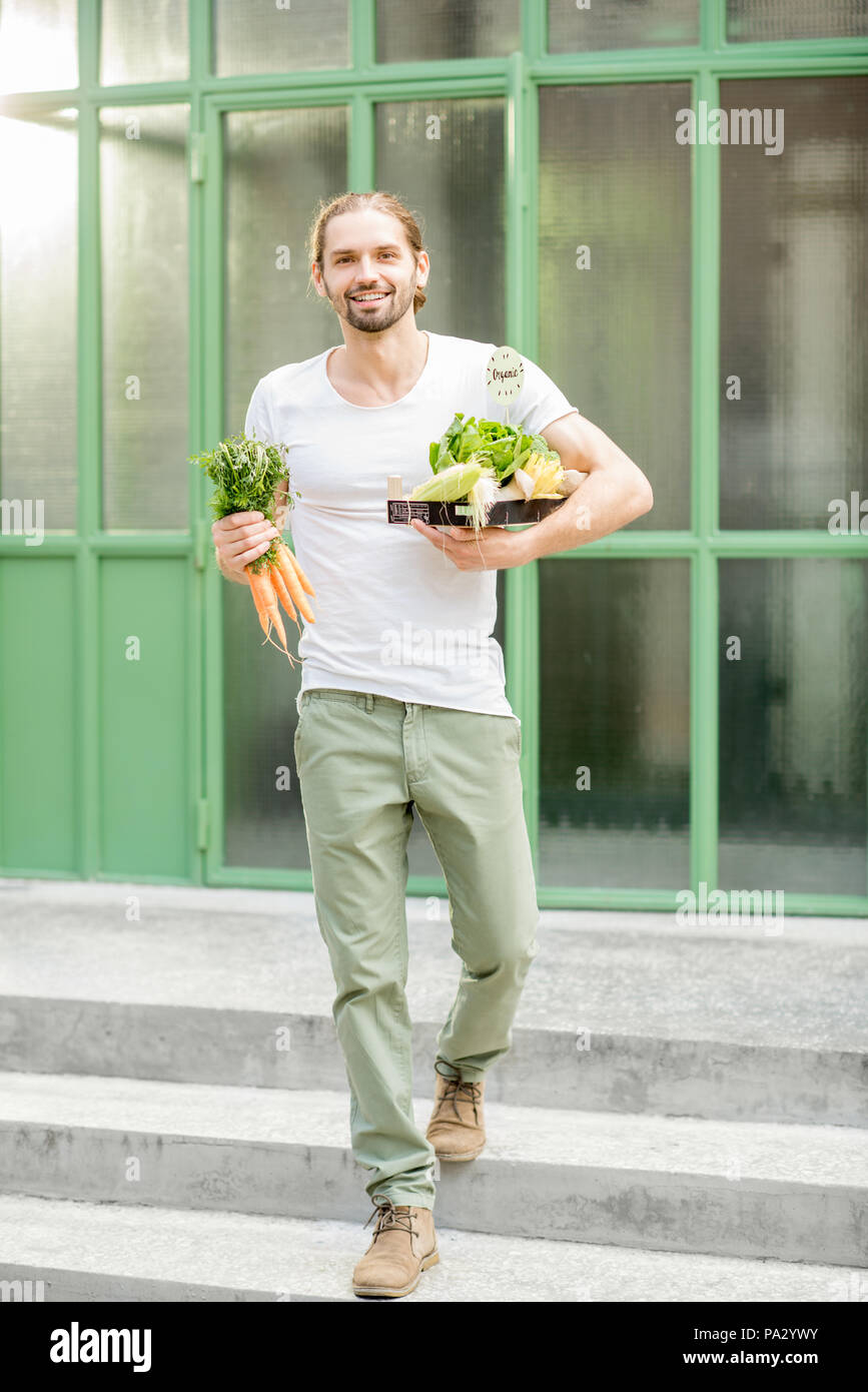 Man carrying box full of fresh raw vegetables just bought at the local market outdoors on the green background - Stock Image