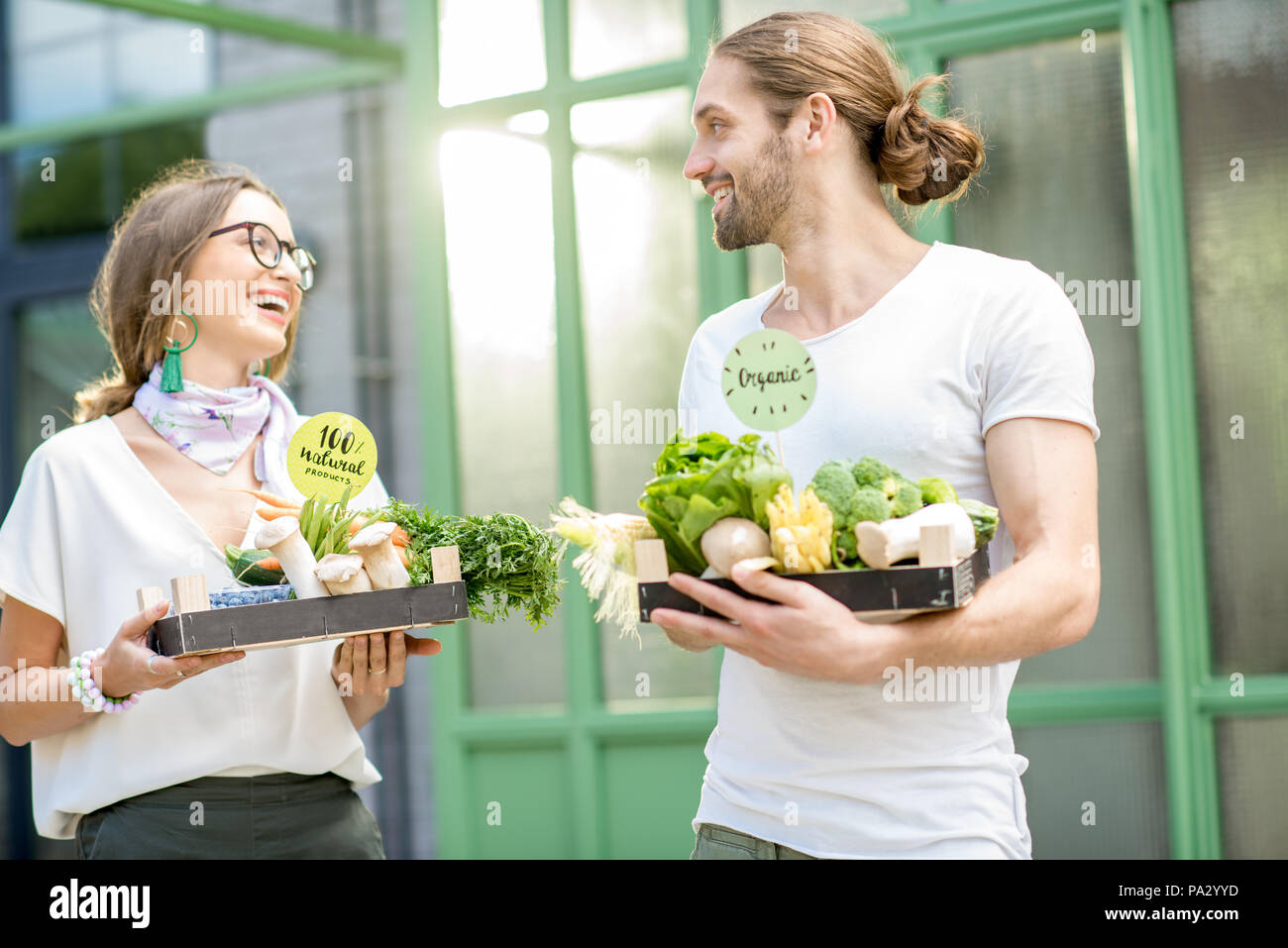 Happy vegetarian couple standing together with boxes full of fresh raw vegetables outdoors on the green background - Stock Image