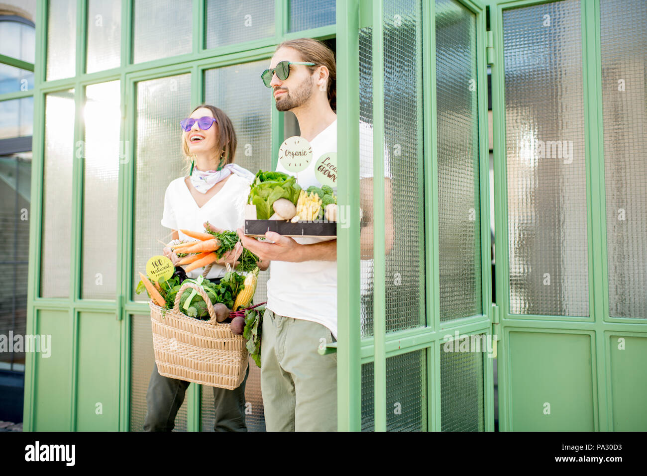 Young vegetarian couple going out the market holding bag and box full of just bought fresh products - Stock Image