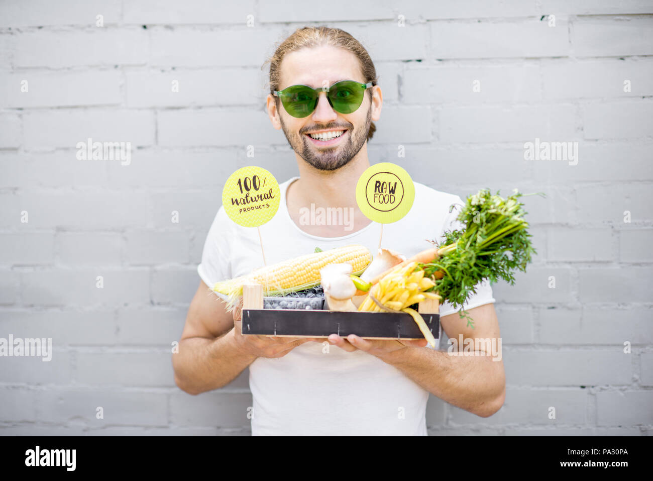 Portrait of a handsome man holding box full of fresh vegetables on the brick wall background Stock Photo