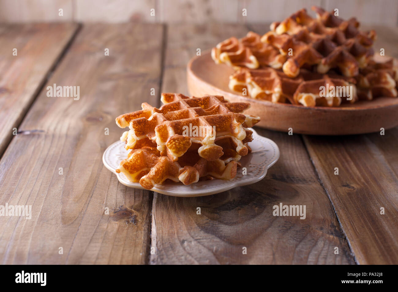 Sweet Belgian waffles for breakfast, on a wooden plate. On a brown wooden background. - Stock Image