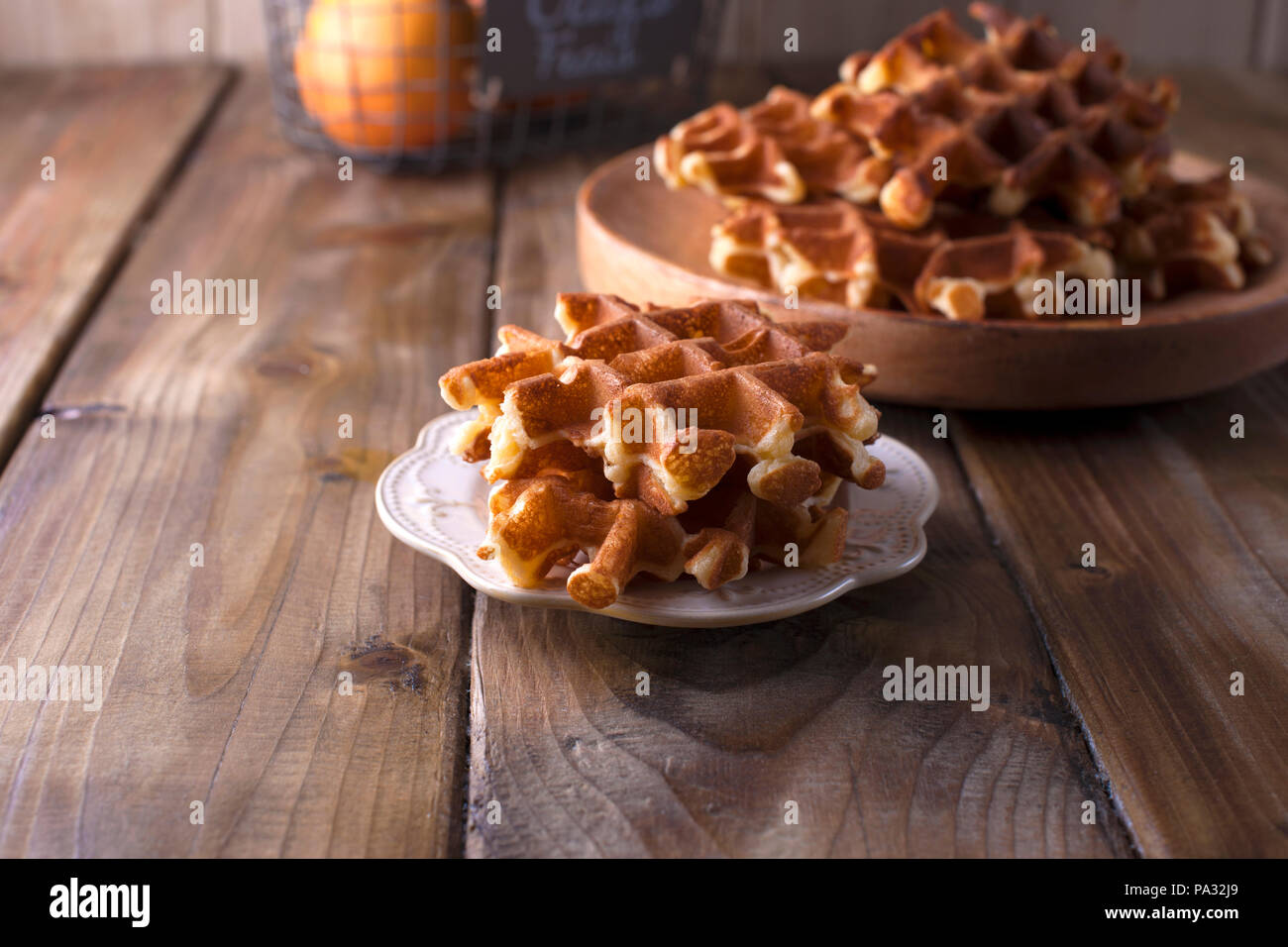 Sweet Belgian waffles for breakfast, on a wooden plate. On a brown wooden background - Stock Image