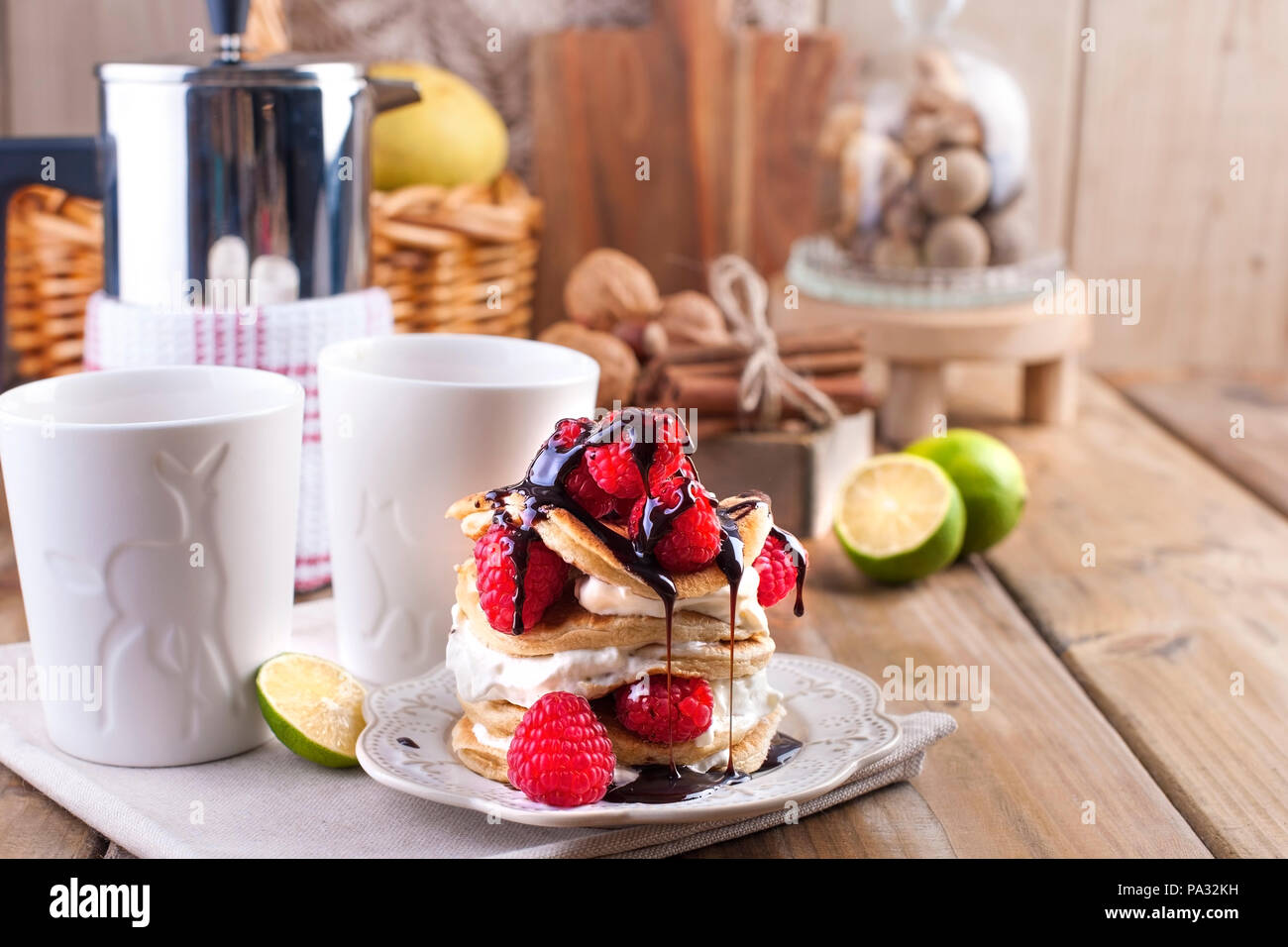 Sweet home punkcakes with white cream and fresh red raspberry berries. Two glasses of tea for breakfast and a kettle. on a wooden background. free space for text or advertising. Stock Photo