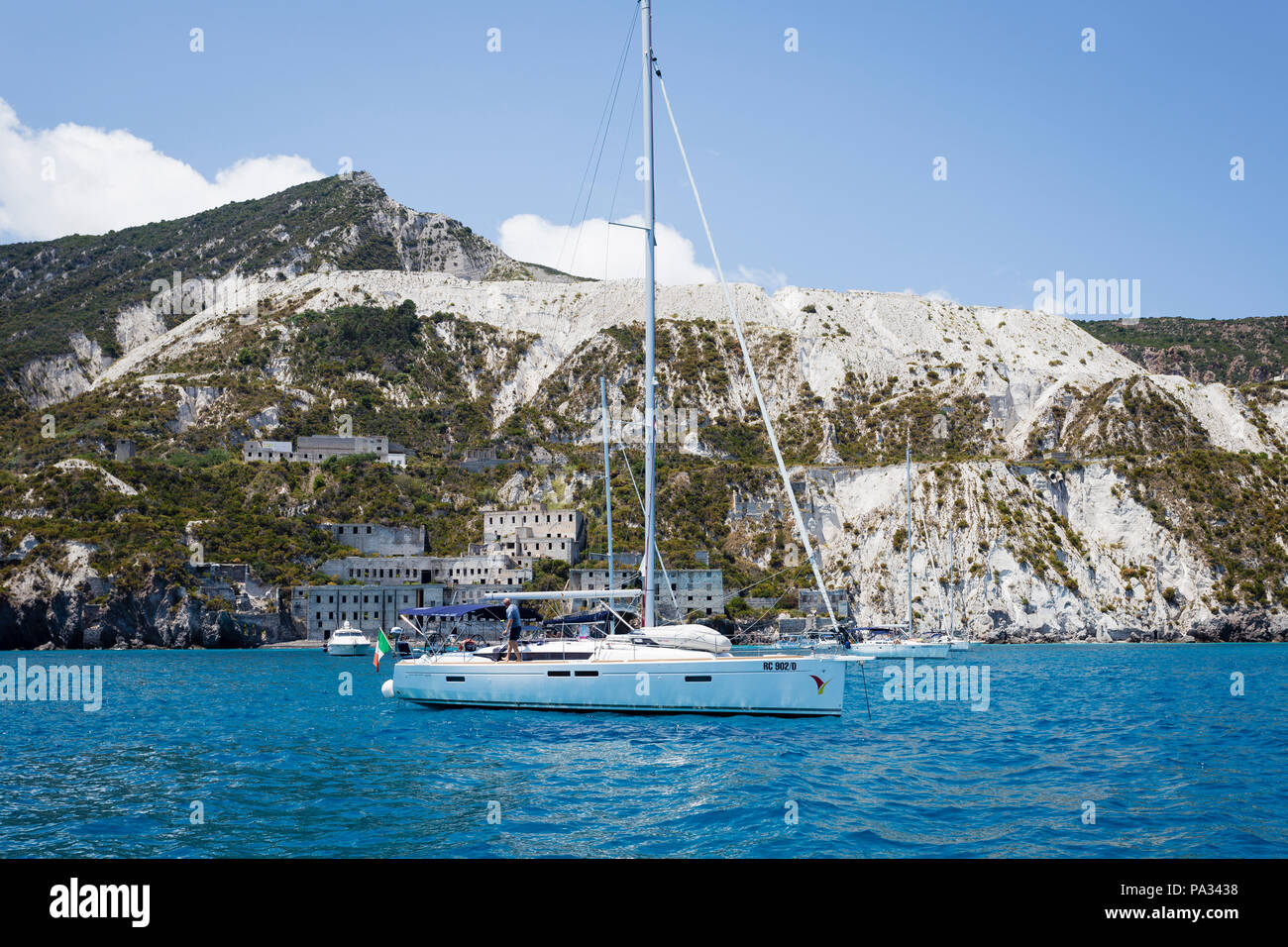 Boats anchored in front of the pumice quarries (cave di pomice) on the island of Lipari, Aeolian Islands, Sicily. - Stock Image
