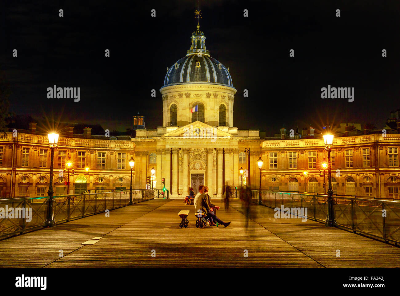 Pont des Arts bridge to Institut de France building, a French learned society group of five academies. Crossing bridge point of view with people in Paris, France. Night scene. - Stock Image
