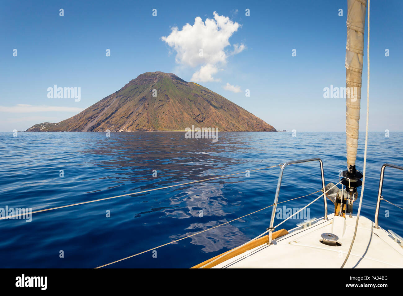 Sailboat approaches the volcanic island of Stromboli, Aeolian Islands, Sicily. - Stock Image
