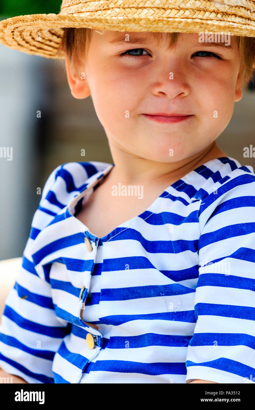 Caucasian blonde child, boy, Barnaby Rudge, wearing Victorian bathing suit and straw hat. Looking at viewer, eye contact. Close up. Dickens Week. - Stock Image