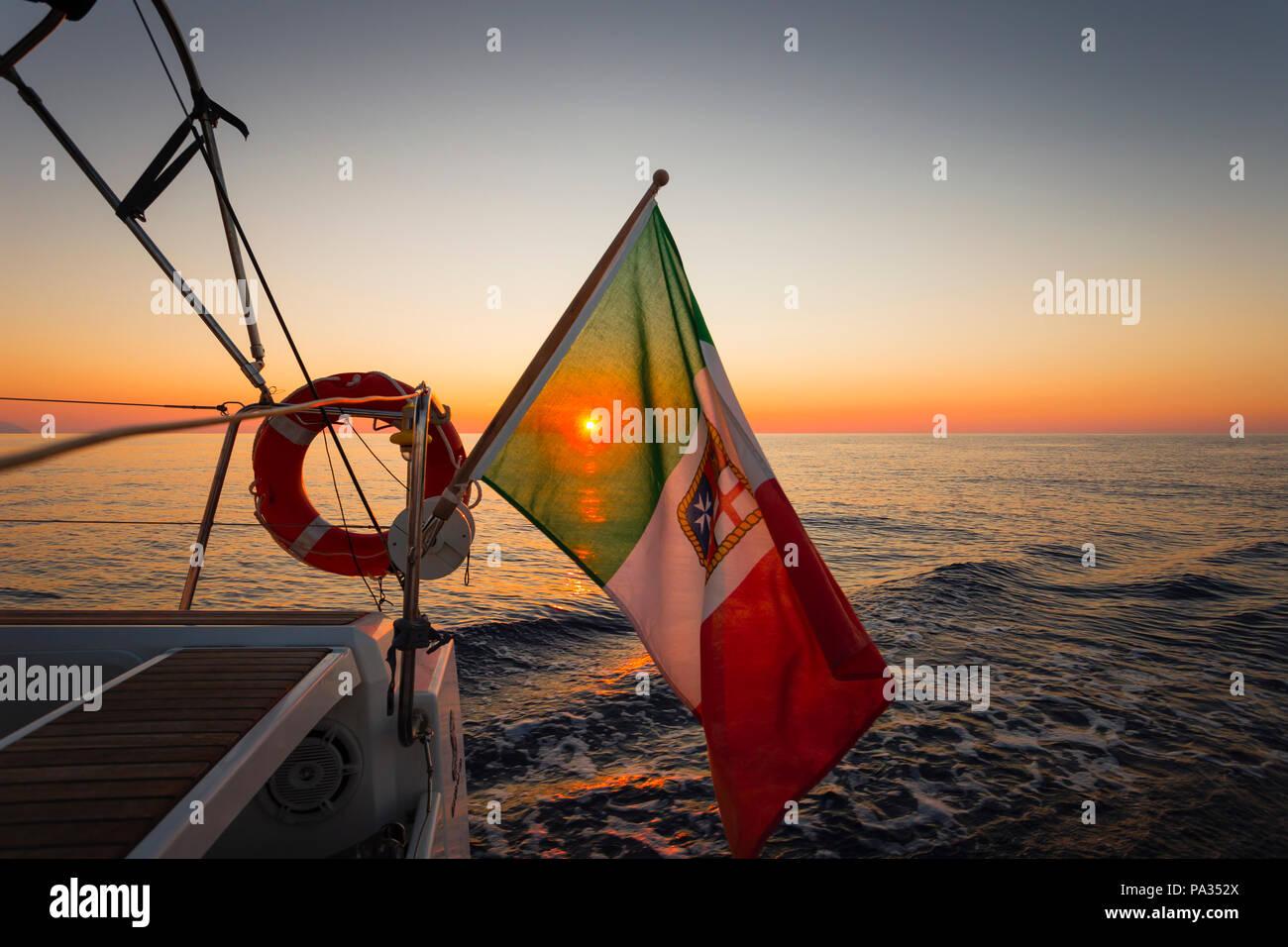 The sun sets on the Tyrrhenian Sea veiled by an Italian nautical flag, Aeolian Islands, Sicily. - Stock Image